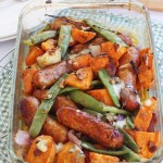 Sausage, sweet potato and orange traybake from above on a green and white checked cloth
