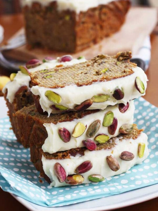 Pieces of banana and pistachio loaf stacked on a blue spotty cloth