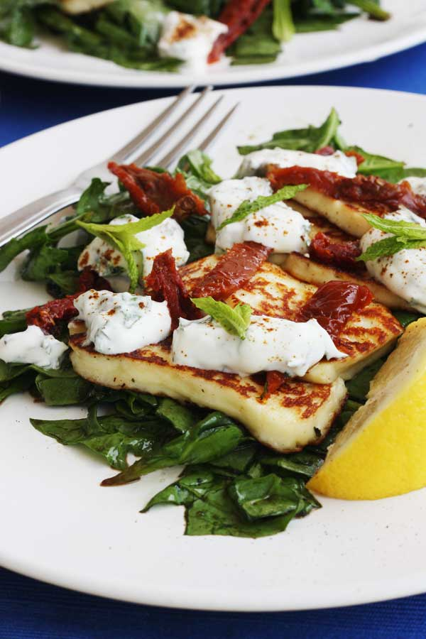 A closeup of a halloumi salad with a fork next to it