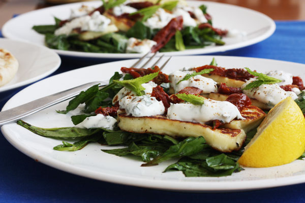 2 plates of halloumi spinach salad with forks on them