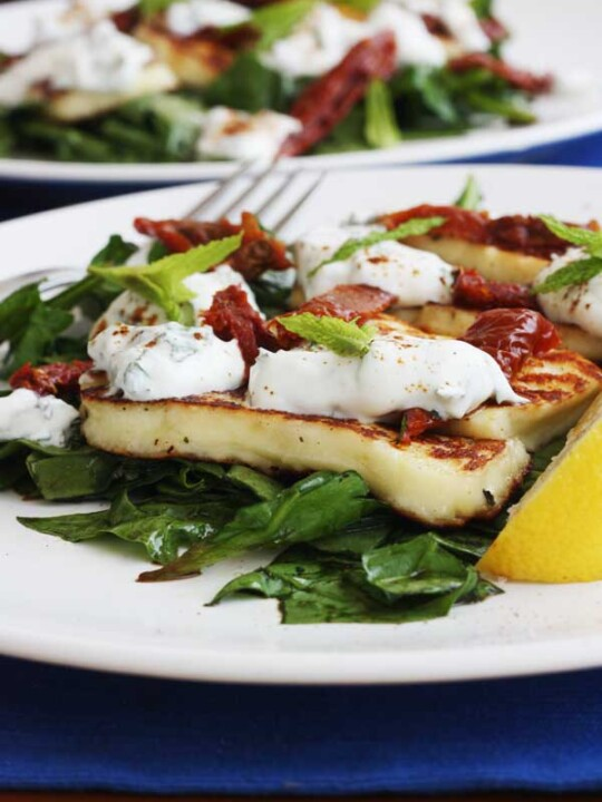 A plate of halloumi salad with another in the background