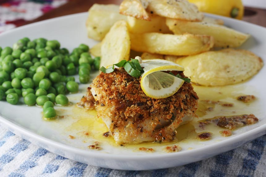 A plate of posh fish and chips with peas on a white plate and on a blue checked tea towel