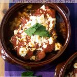 Greek style baked eggplant with tomato sauce and feta cheese in a brown pot