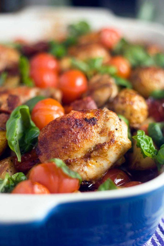 Closeup of a blue baking dish of chicken, chorizo and patatas bravas