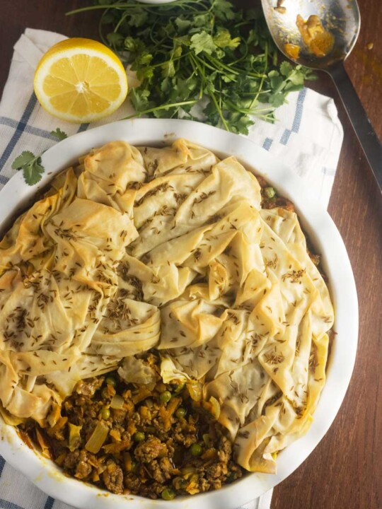 an overhead photo of a samosa pie with a scrunched filo pastry top