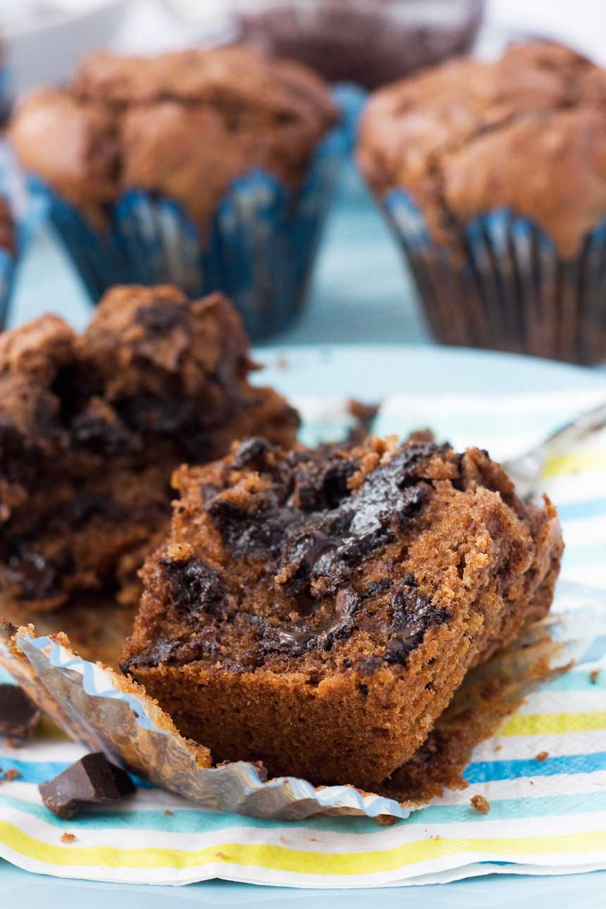 A soft-centred triple chocolate muffin sliced in half on a plate - there are more muffins in the background