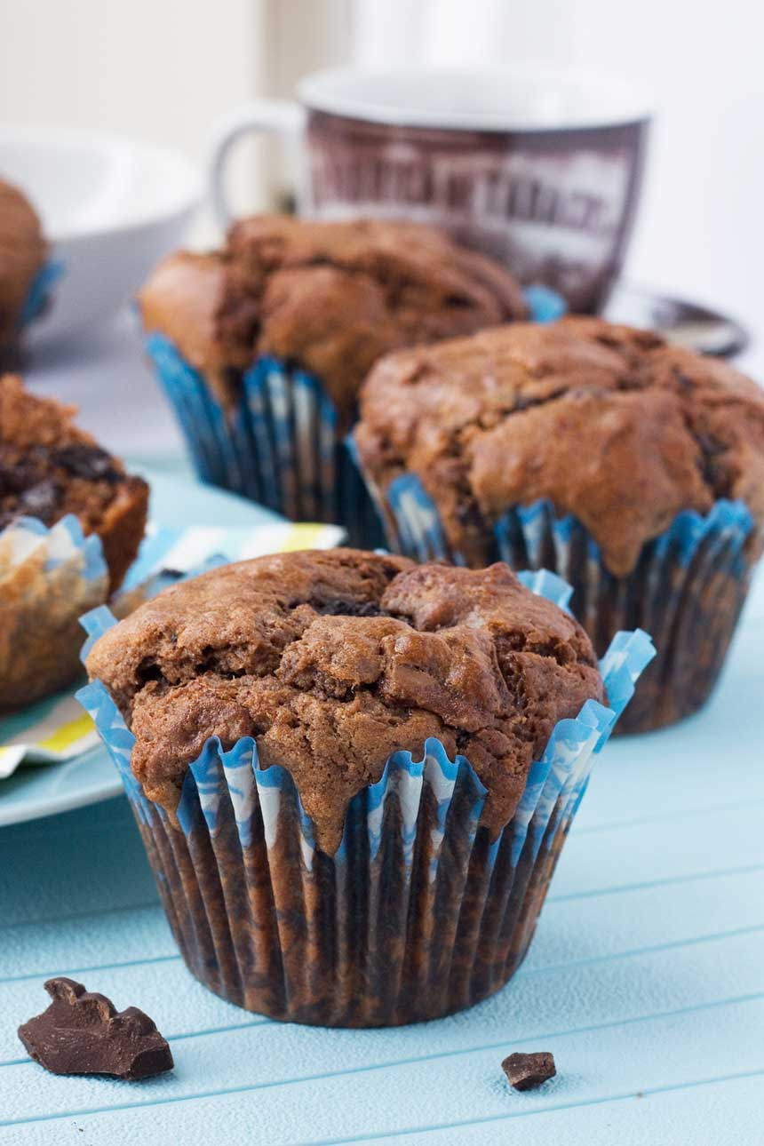 Soft-centred triple chocolate muffins on a blue background