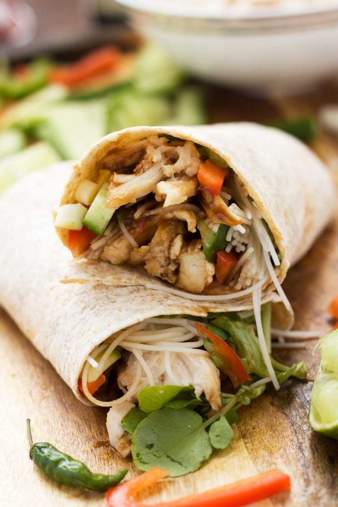 2 halves of a hoi sin chicken noodle wrap lying on a wooden board on top of each other