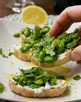 Someone taking a broad bean, mint and ricotta crostini off a plate of 4 with a lemon and checked cloth in the background