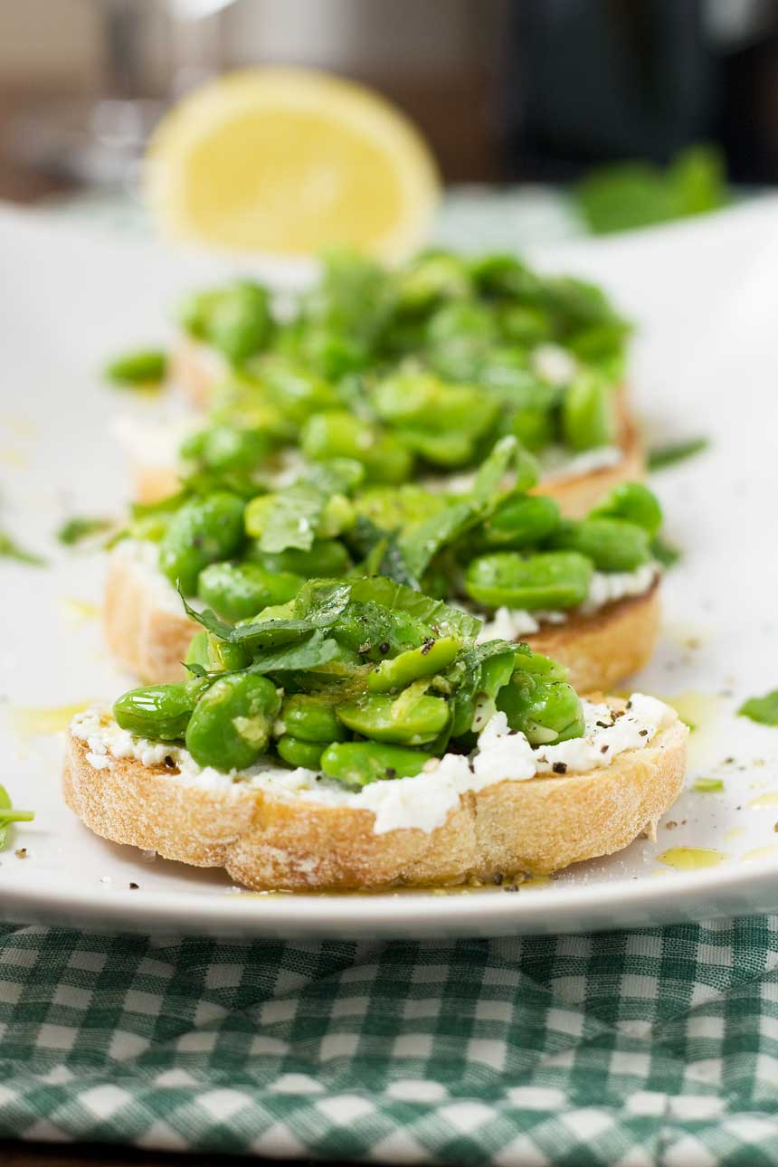 A close up of a fava bean, mint and ricotta crostini on a white rectangular plate - there are more in the background
