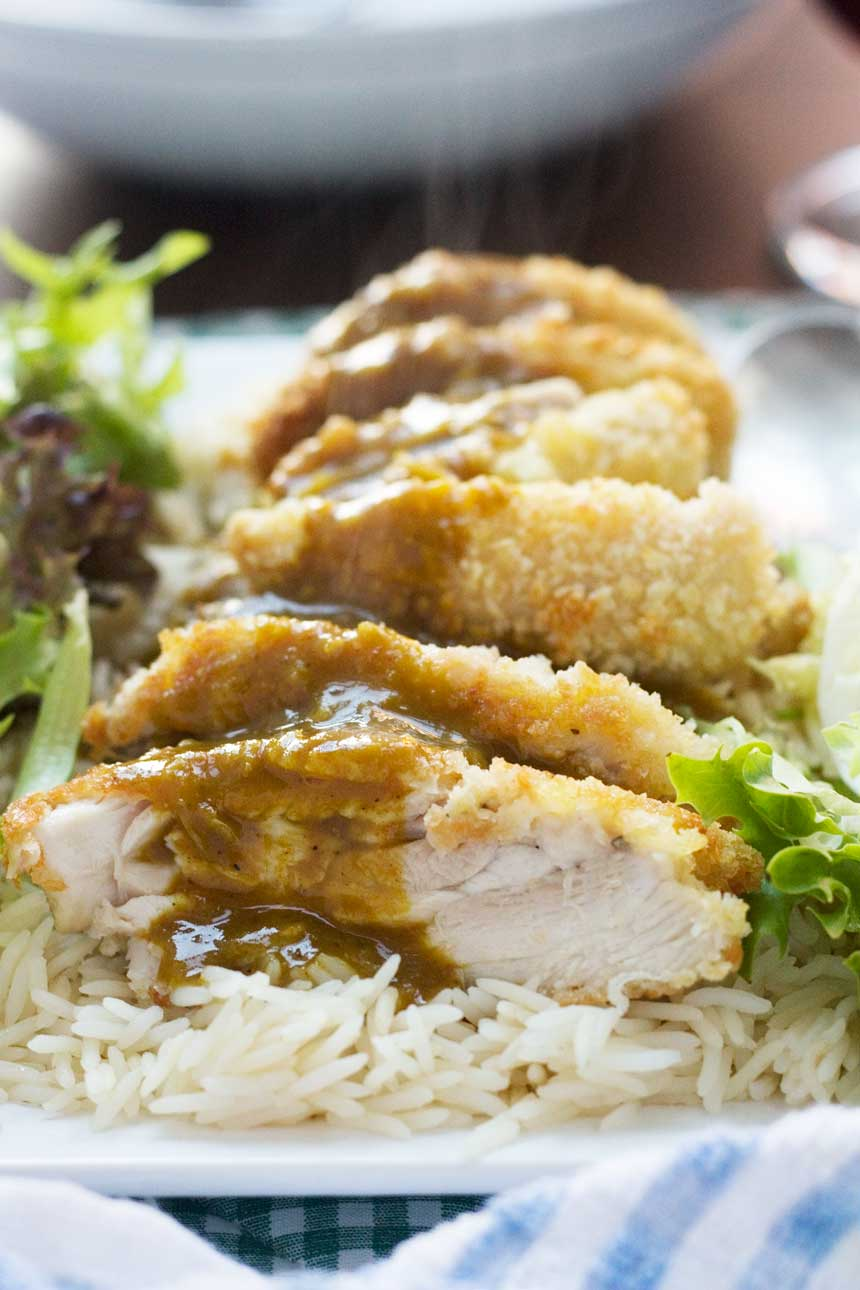A close up of a chicken katsu with curry sauce meal on a bed of rice and lettuce