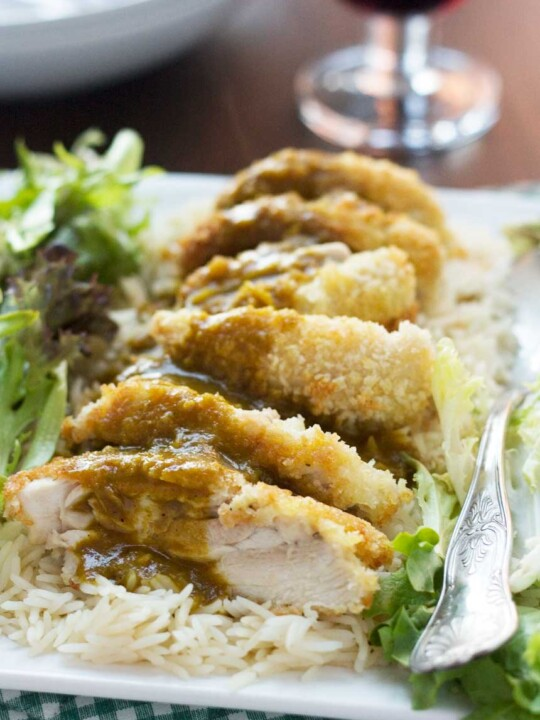 A close up of a chicken katsu curry with an easy curry sauce on a bed of rice and with lettuce