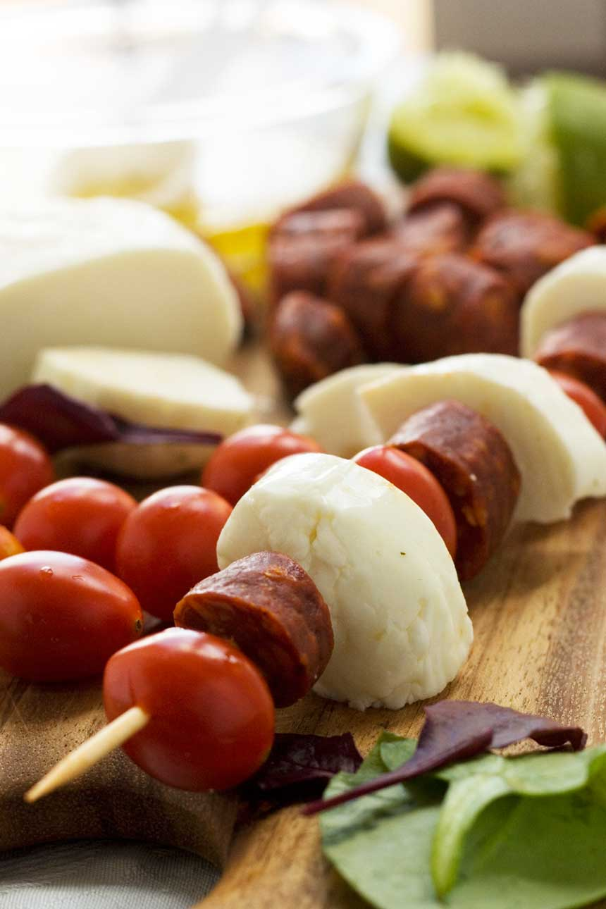 Raw halloumi, chorizo and tomato skewers on a wooden board