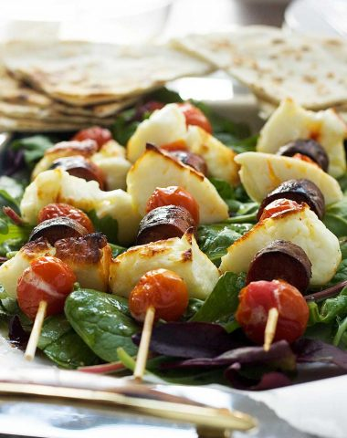 A close up of halloumi, chorizo and tomato skewers on a bed of lettuce with pitta bread in the background
