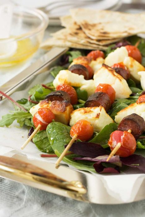 Halloumi and chorizo skewers on a bed of greens and on a metal tray