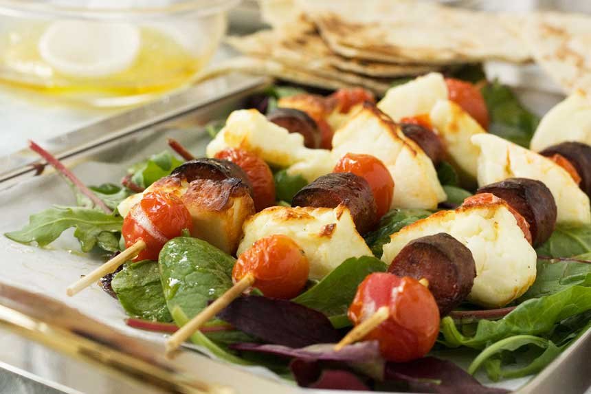 Halloumi chorizo and tomato skewers on a silver tray with pitta bread in the background