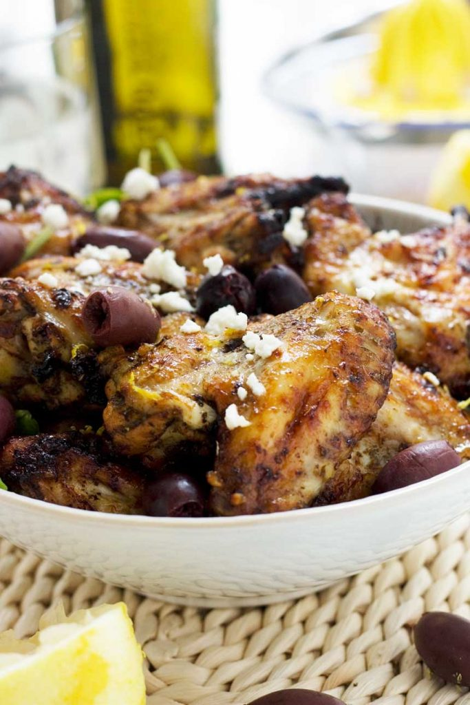 A big bowl of Greek baked chicken wings with olives and feta sprinkled on top