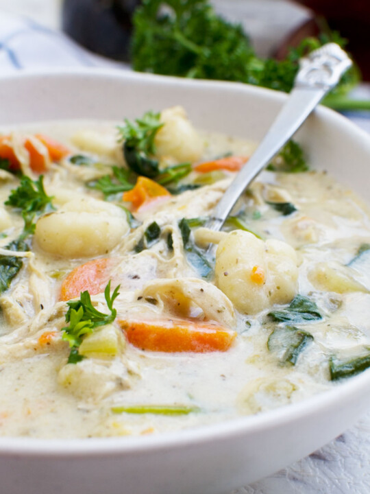 A close up of crockpot chicken gnocchi soup in a white bowl with a spoon
