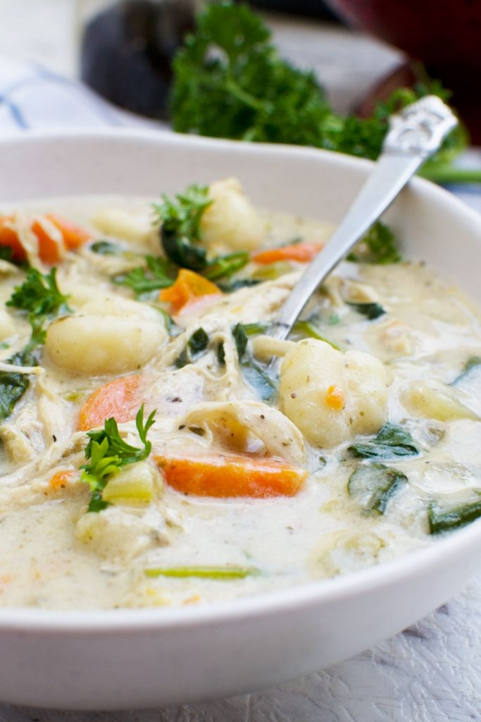 A close up of crockpot chicken gnocchi soup in a white bowl