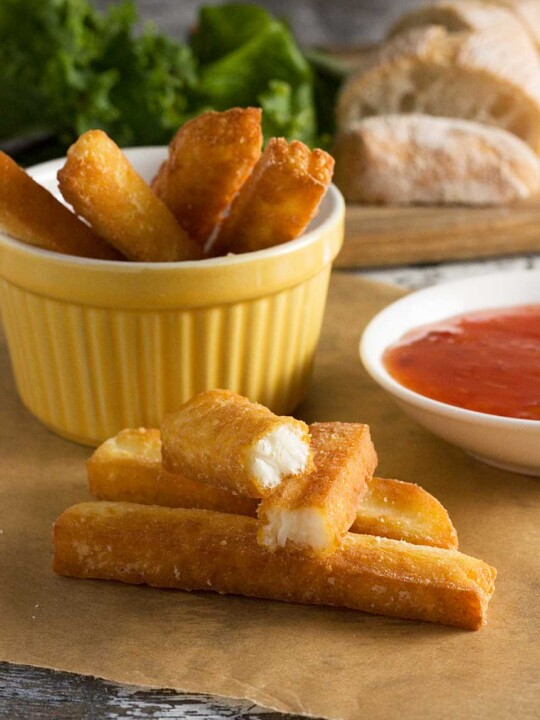 A small stack of crispy halloumi fries with more in a dish in the background