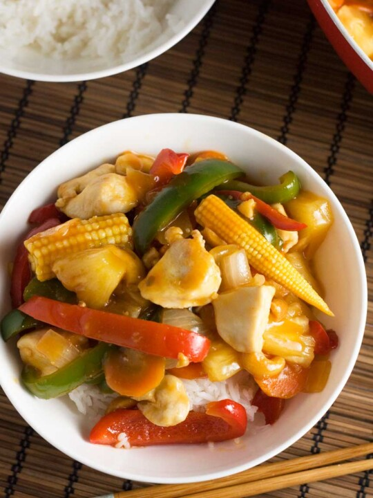 An overhead shot of a dish of quick sweet and sour chicken on a brown place mat