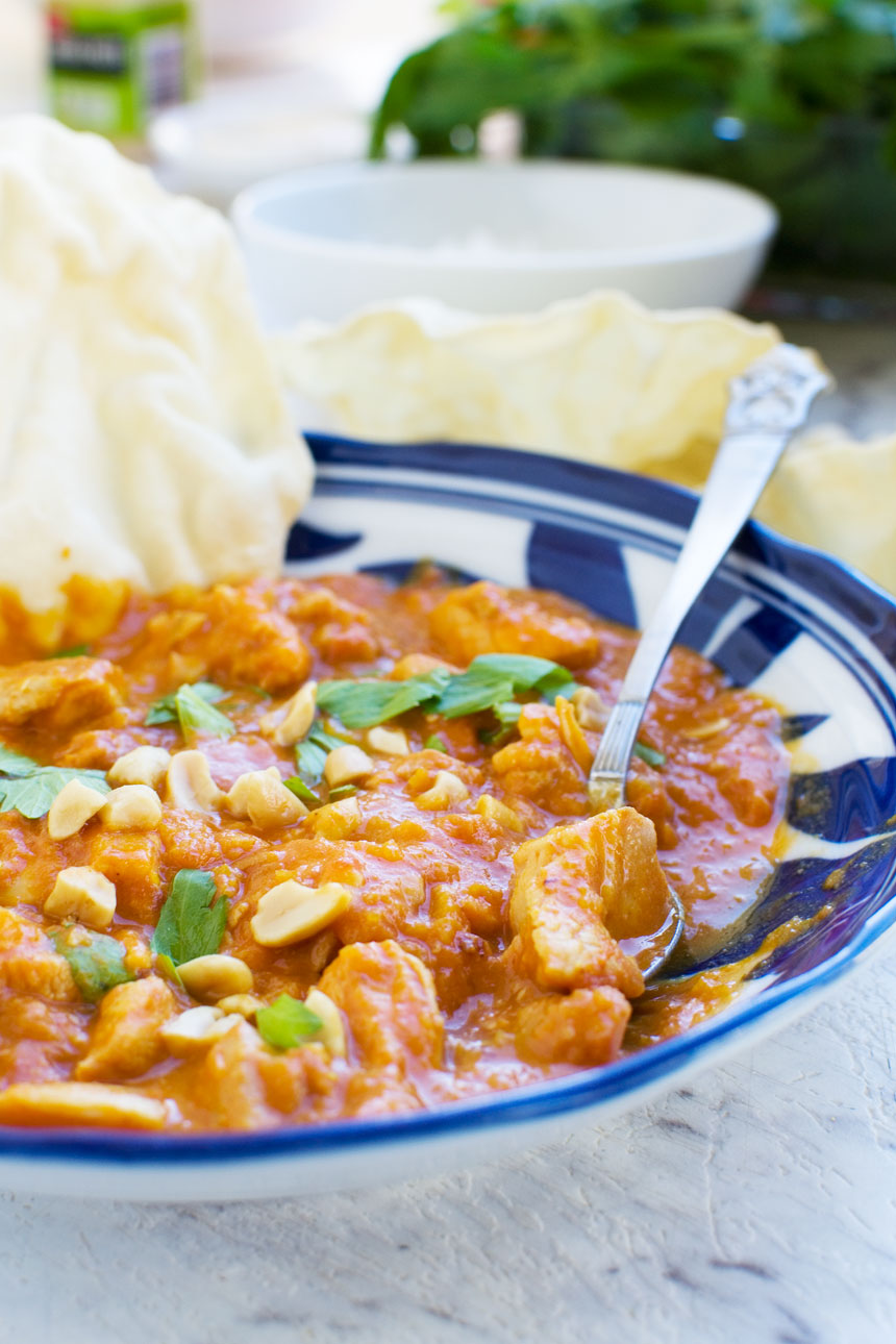 A Thai chicken and butternut squash curry with peanuts, coriander and poppadoms, with a spoon in it