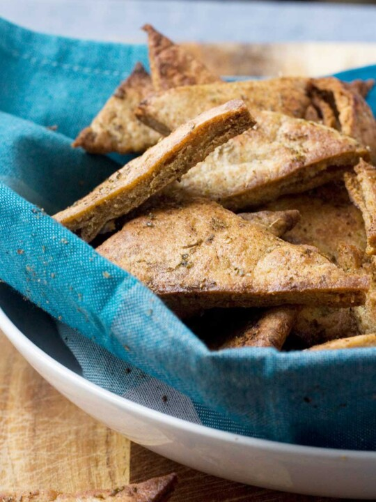 A big bowl of homemade Greek pita chips nestled inside a blue tea towel