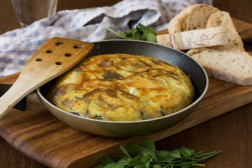 A whole Spanish omelette in an omelette pan with ingredients in the background