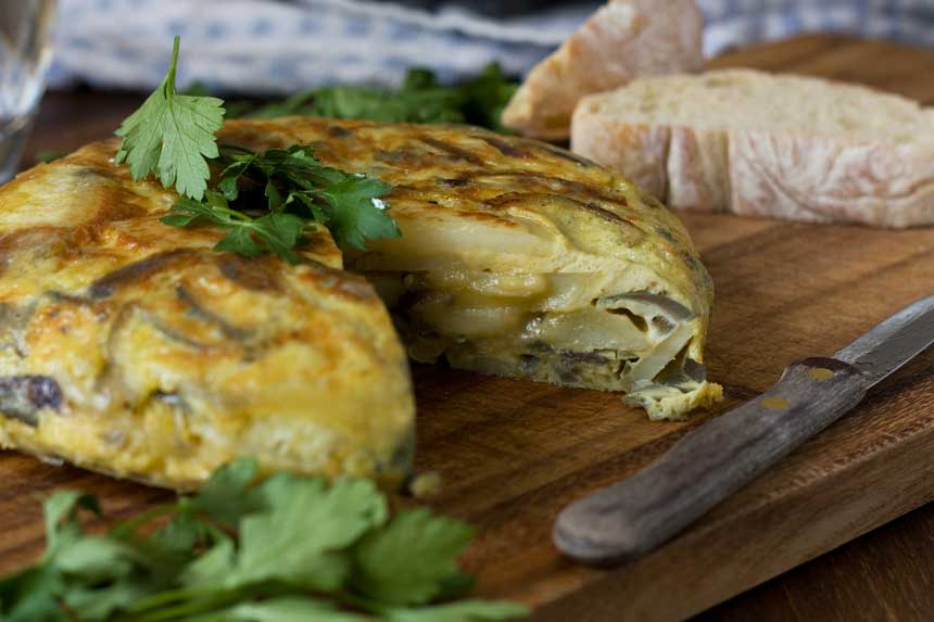 A close up of a Spanish tortilla or omelette with a big slice cut out of it on a cutting board with bread in the background
