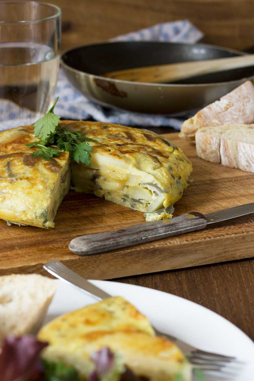 A Spanish omelette on a wooden cutting board with a slice out of it and another piece in the foreground