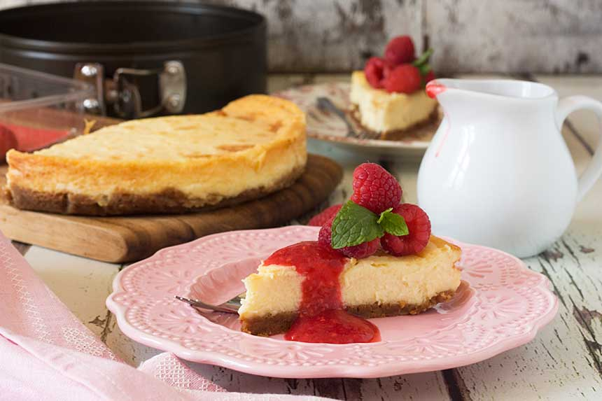 A piece of white chocolate baked cheesecake on a pink plate with the rest of the cake in the background and on a white background