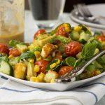 A square plate of crispy halloumi salad with tomato, corn and avocado on a white and blue tea towel