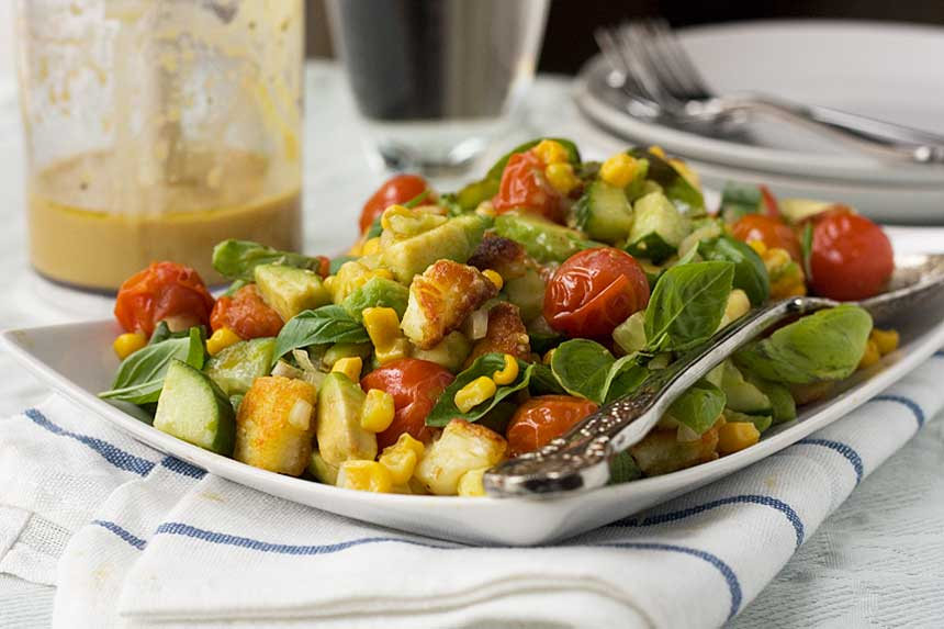 A square plate of crispy halloumi salad with tomato, corn and avocado on a white and blue tea towel