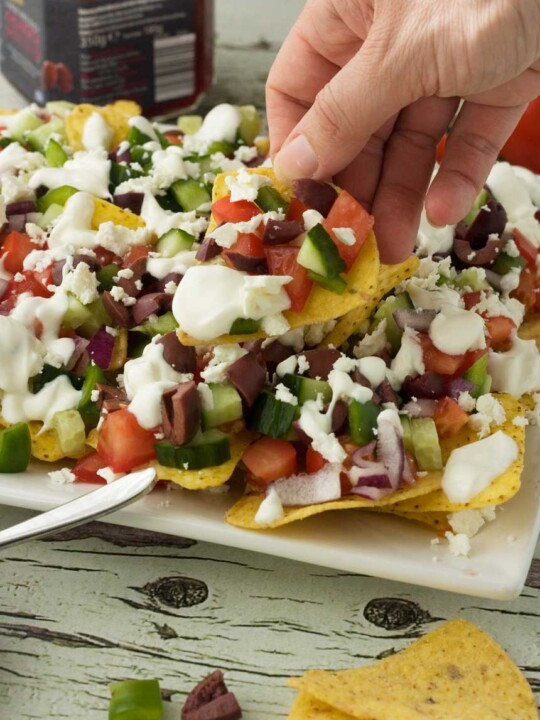 Some holding a loaded Greek nacho above a white plate of them