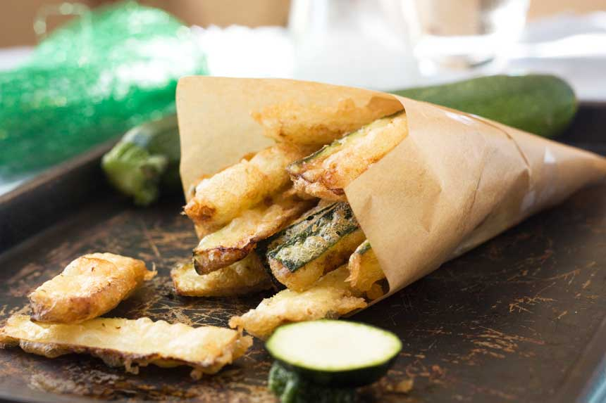 A brown baking paper bag of zucchini fries