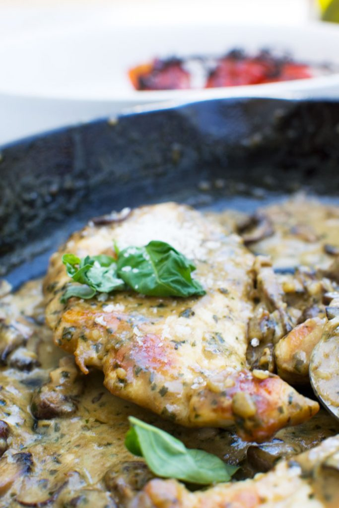 Close up of creamy pesto chicken with parmesan and mushrooms in a cast iron pan