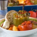A colourful dish of Greek stuffed tomatoes and peppers with bread and feta - there's a baking dish in the background