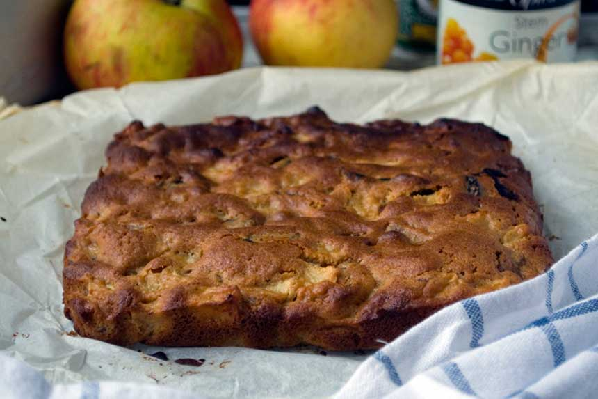 Whole sticky apple ginger cake bars on baking paper with apples and other ingredients in the background