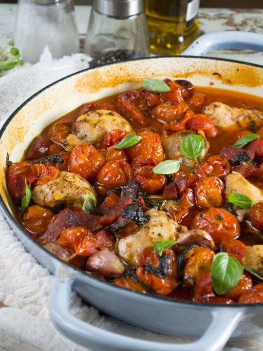 Half a pan of chicken and chorizo with cherry tomatoes with a white tea towel