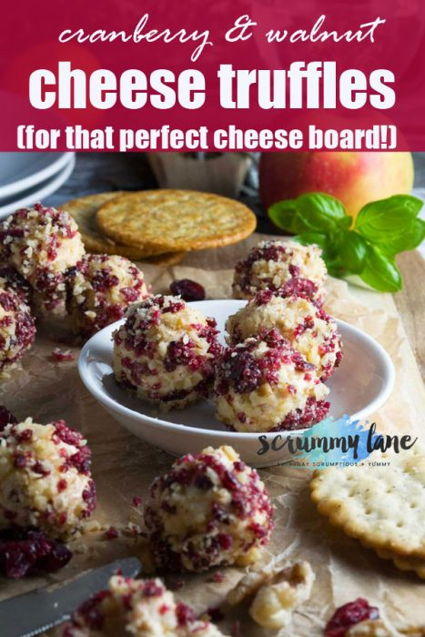 cheese truffles with cranberries and walnuts on a cheese board for Pinterest