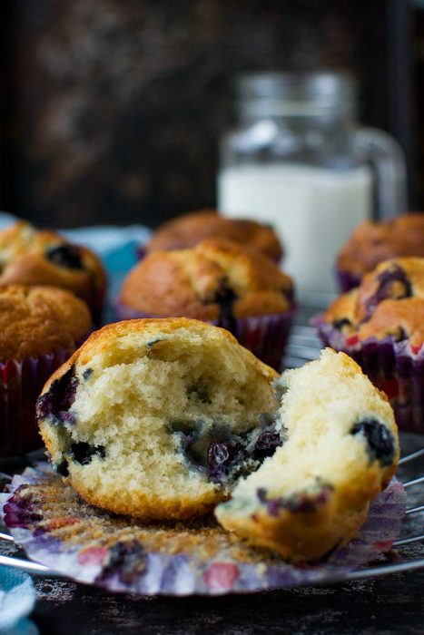 The inside of a Greek yogurt blueberry muffin on a cooling rack with more muffins