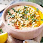 An clay pot of hummus with pine nuts and olive oil, served with 2-ingredient flatbfread