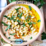 A clay pot of classic hummus sprinkled with pine nuts and paprika - image for Pinterest