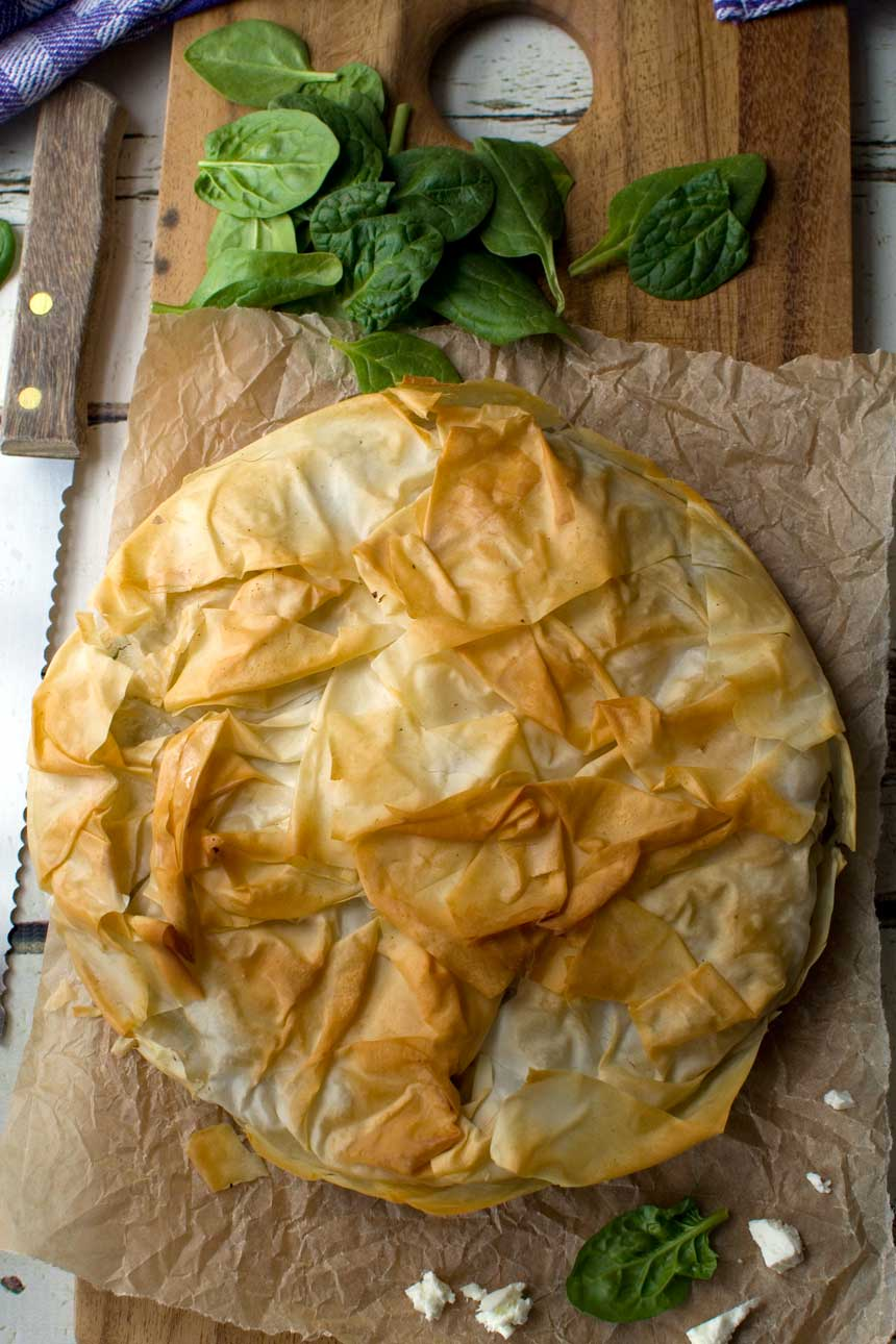 A spinach and feta filo pie on a cutting board from above.