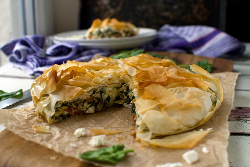 A whole Greek spinach and feta filo pie on baking paper with a piece cut out and with a piece in the background on a plate