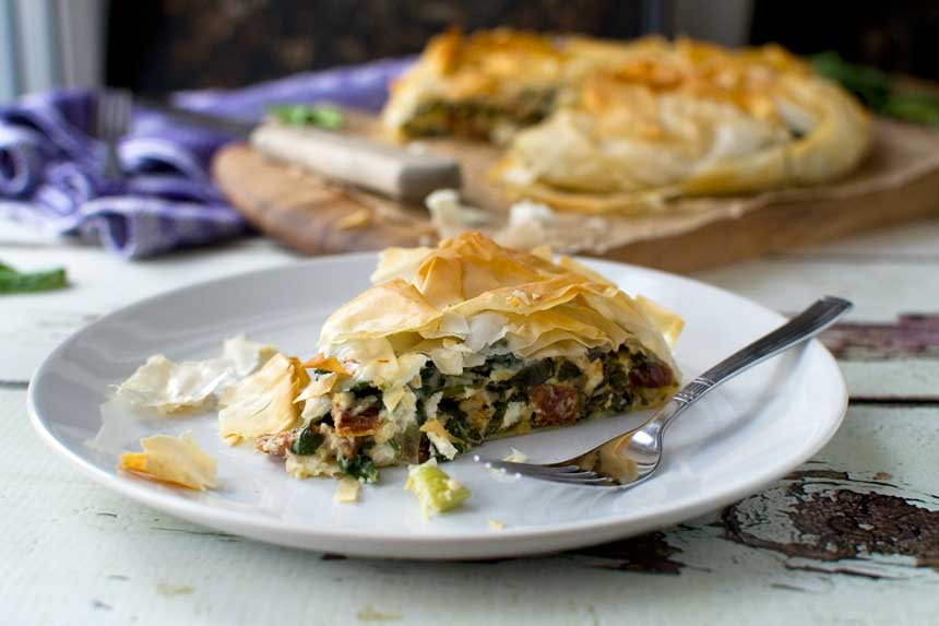 A piece of spinach and feta filo pie on a plate with the rest of the pie in the background.