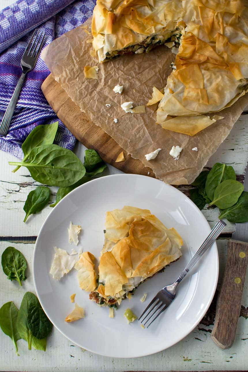 A piece of spinach and feta filo pie on a plate photographed from above