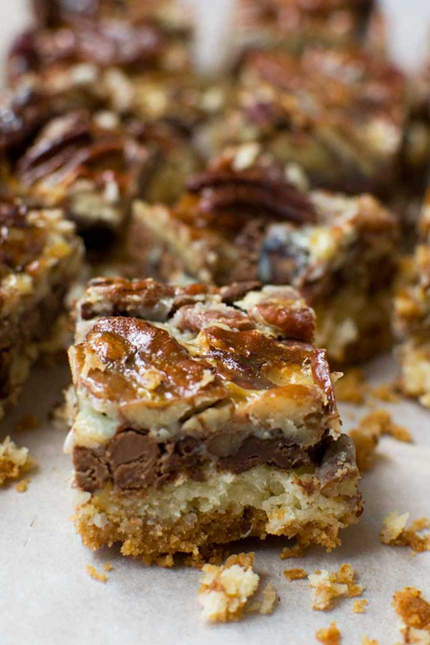 A close up of a no bowl chocolate pecan bar with others in the background