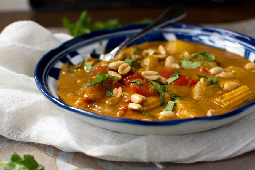 A horizontal image of a dish of Thai Massaman chicken curry with sweet potatoes and peanuts