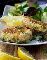 Basic crispy salmon fishcakes on a rectangular plate with salad and lemon wedges in the background
